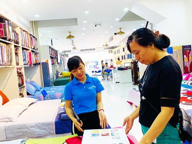 Nhân viên tư vấn chăn ga gối đệm cho khách hàng tại nhà phân phối Đông Á